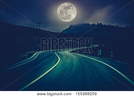 Landscape of full moon with curvy roadway in forest at national park. Mountain winding road passing outdoors at night. Cross process and dark tone.