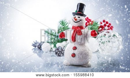 Christmas snowman. Holiday greeting card copyspace. Fairy-tale personage with branch tree and balls. Decoration winter still life. Falling snow
