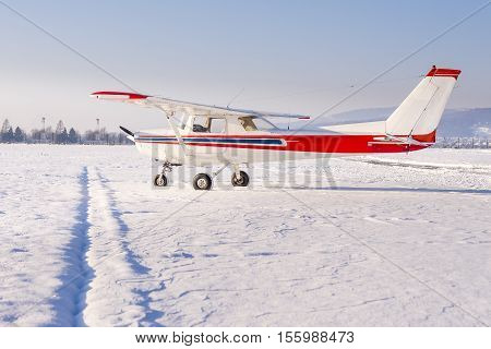 Small sport airplane with white fuselage and red and blue stripes on the apron. The airport is covered in fresh snow on a sunn day.