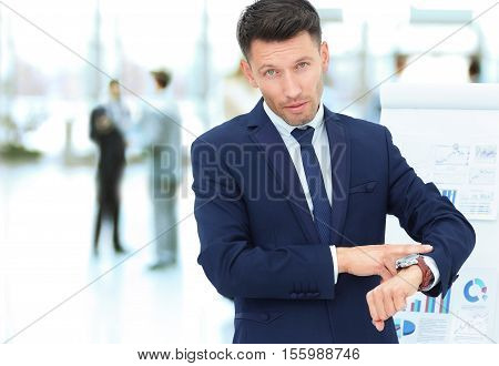 closeup of a businessman points to his watch on the background of the financial schedules