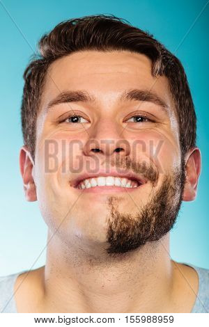 Portrait of happy man with half shaved face beard hair. Smiling handsome guy on blue. Skin care and hygiene.
