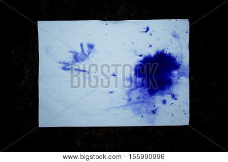 Blue blot of ink on a sheet of white paper on the isolated black background. Blue colorful spot on white paper with empty place. Abstract base basis background backdrop. Space for text