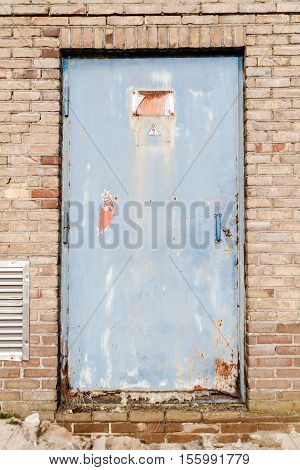 Rusty high voltage warning sign at a old metal door background