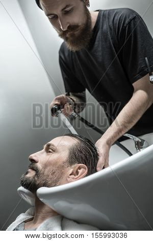 Satisfied man with a beard lies on the white sink in the barbershop. Brutal barber with a tattoo and a big beard is washing his head. Guy has a white towel. Vertical.