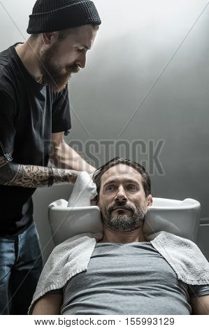 Brutal man with a beard lies on the white sink in the barbershop. He wears a gray T-shirt with a white towel. Bearded barber with a tattoo dries his head with a towel. Vertical.