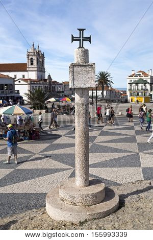 NAZARE, PORTUGAL - September 13, 2016: Limestone memory pillar with inscription and Order of Christ Cross located on the hilltop O Sitio overlooking Nazare Portugal