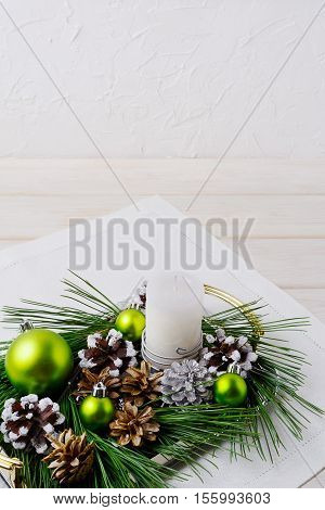 Christmas background with snowy pinecone and green ornaments. Christmas party decoration with shiny balls. Copy space.
