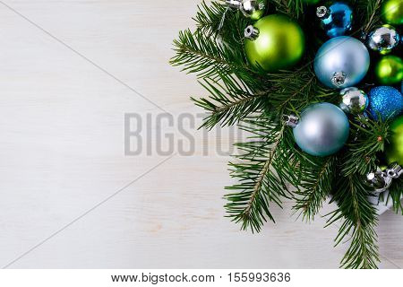 Christmas table centerpiece with fir branches blue and green ornaments. Christmas party decoration with shiny balls. Christmas greeting background. Copy space.