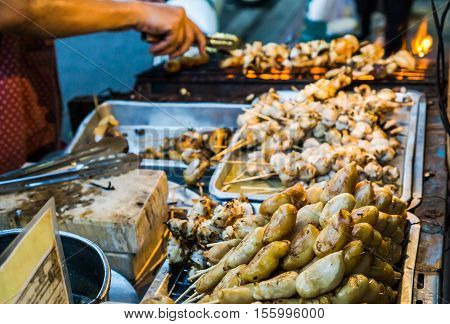Evening street food in Bangkok, Thailand : Grilled squid on gridiron in evening street market, Squid charcoal barbecue in Thai street food market
