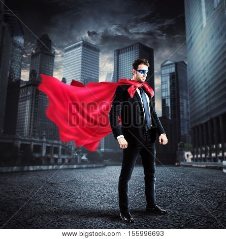Businessman with a superhero cape and mask lands on the asphalt of a city street