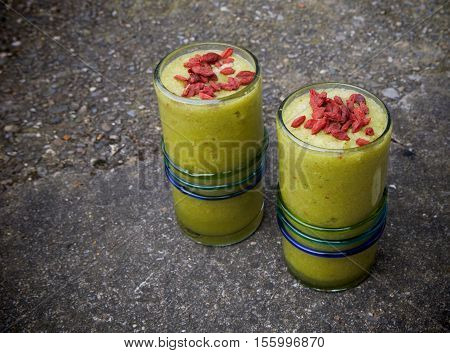 Healthy drink green smoothies with red goji berries on top