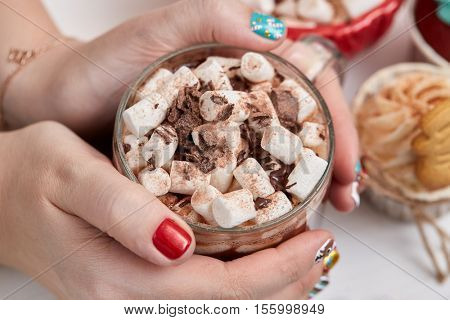 Female hands with bright festive manicure design holding glass mug with hot cocoa and marshmallows. 