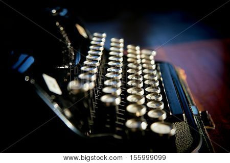 Old black typewriter on dark background with shiny keys side view
