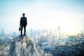 Back view of young man in suit and with briefcase in hand standing on mountain top. City background with copy space. Leadership concept poster
