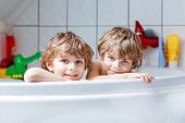 Happy siblings: Two little twins children playing together with water by taking bath in bathtub at home. Kid boys having fun together, helping with hair washing. poster