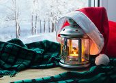Lantern with candle and Christmas Santa hat on the windowsill and winter forest outdoors-Christmas and New Year winter background. Christmas concept. Festive Christmas winter still life. Christmas in home-holiday Christmas background poster