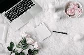 Freelance fashion comfortable feminine workspace in flat lay style with laptop, vintage tray, roses, candles, notebook and pen on white fur background. Top view, flat lay. Freelance concept. poster