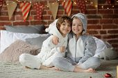 Christmas. Two children in pajamas sitting on the bed waiting for Christmas gifts. The bedroom is decorated with festive garlands. Children happily embrace. Merry Christmas. Happy Christmas. poster