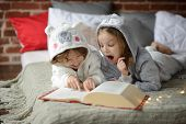 Two children brother and sister lie on big bed and read fairy tales. Children dressed in fluffy pajamas like little cute animals. Before them the huge book. Children are keen on reading. poster