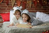Christmas Holidays. Two children lay on a bed in soft pyjamas. Bedroom is decorated by christmas garlands. The children read a great book with Christmas tales. Christmas - magic time. Merry Christmas. poster