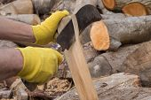 Gloved hands cutting firewood with a reaping hook poster