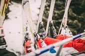 Four unrecognizable skier driving on ski lift. Focus of a skis. poster