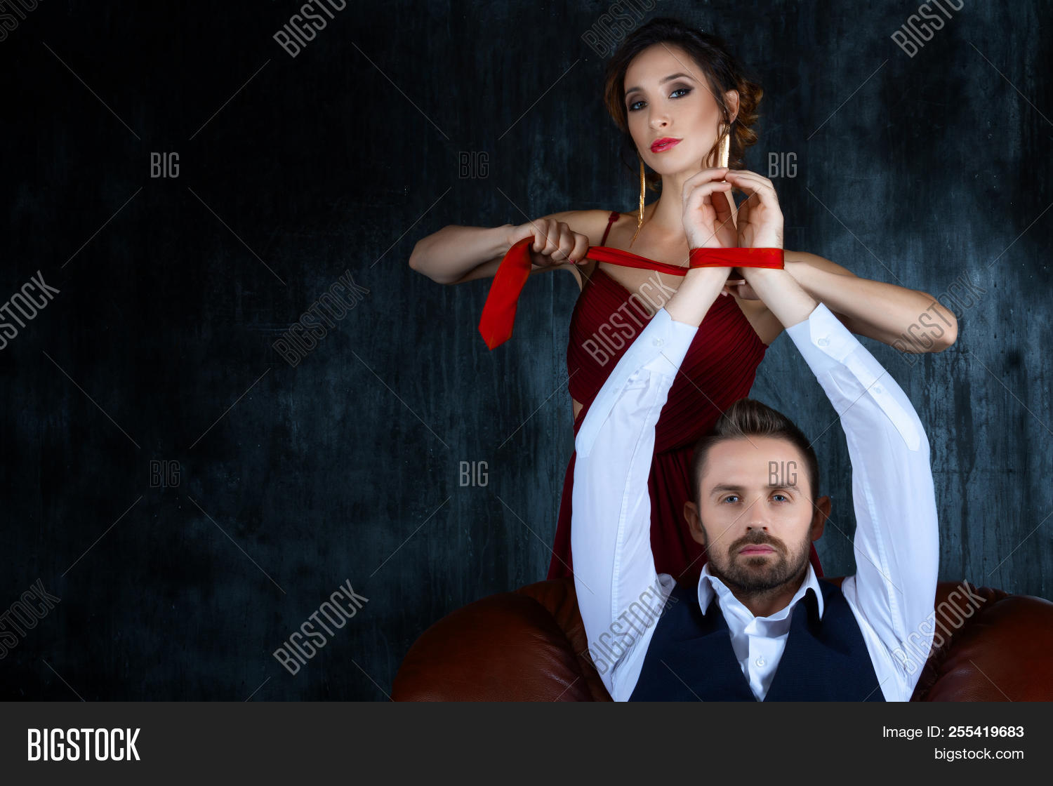 88481c33d80c Couple in dating. Rich man male dressed skirt sitting with tied hands.  Woman female in expensive red evening dress tying hands of man by red tie.