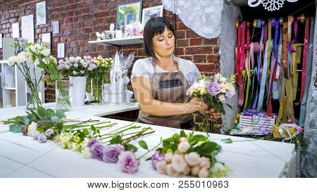 Professional Caucasian Female Florist Master Preparing And Selecting Rose Branches For Flower Bouque