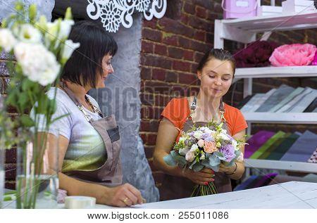 Professional Florists Arranging Wedding Bouquet In Floral Design Studio. Caucasian Women In Aprons C