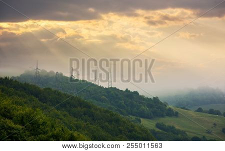 Foggy Autumn Countryside In Mountains. Power Line Tower On The Forested Hill Touch The Cloud. Beauti