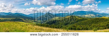 Panorama Of A Beautiful Landscape. Grassy Meadows And Forested Hills In Early Autumn. Mountain Ridge