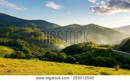Mountainous Countryside In Evening. Fog Or Fire Rise Behind The Cliff. Asphalt Road In The Distance