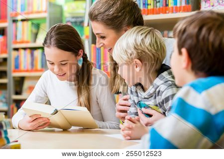Teacher with her class visiting the library reading books for education