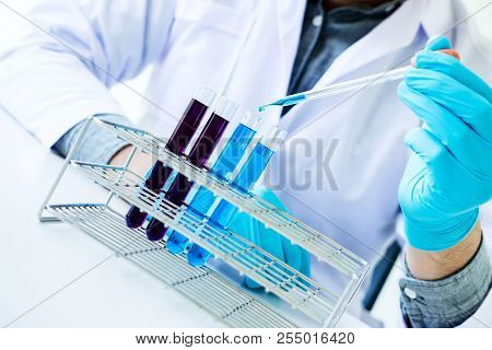 Biochemistry laboratory research, Chemist is analyzing sample in laboratory with equipment and science experiments glassware containing chemical liquid. poster