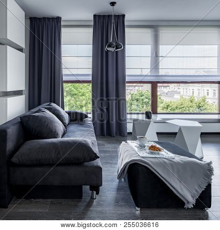 Gray Living Room With Sofa, Pouf Coffee Table And Big Windows With Blinds And Curtains