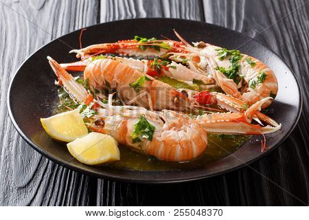 Freshly Cooked Langoustines, Scampi With Lemon And Tasty Sauce With Herbs Close-up On A Plate. Horiz