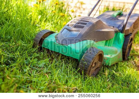 Lawn Mower Cutting Green Grass In Backyard In Sunny Day. Gardening Country Lifestyle Background. Bea