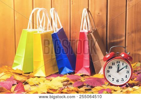 Color Shopping Bags On Fallen Leaves Background, With Retro Alarm Clock. Time For Seasonal Sales. Au