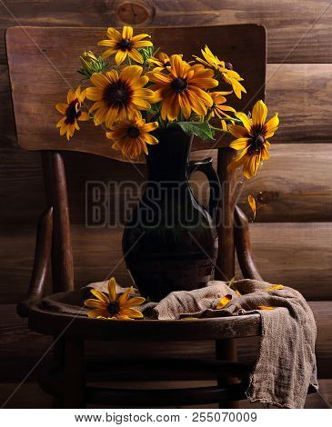 Yellow Flowers In A Jug On A Wooden Chair