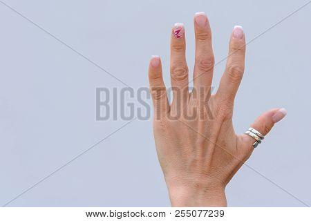 Hand of an older woman with manicured nails wearing a silver thumb ring with splayed fingers over a white background with copy space poster