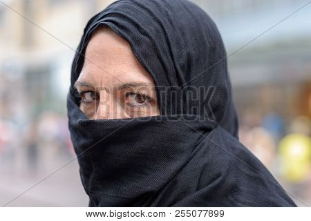 Woman Wearing A Hijab With Mouth And Lower Face Covered Glancing Sideways At The Camera With A Thoug