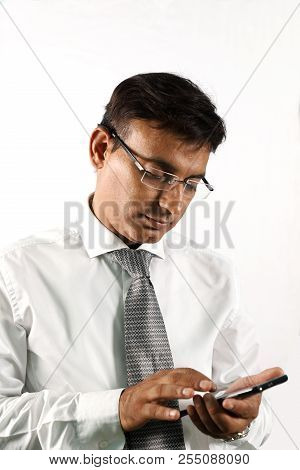 Portrait Of Indian Male Working On A Smart Phone Isolated On White Background