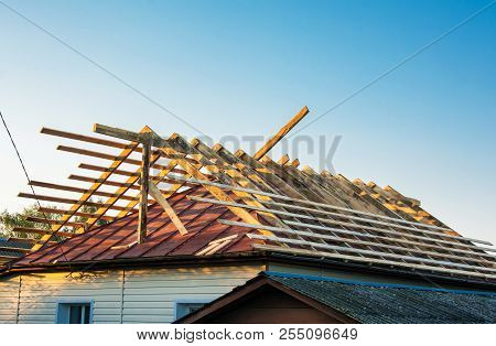 Wooden Roof Frame House Construction. Wooden Rafters Of New Roof Above Old Roofing. Replacing An Old