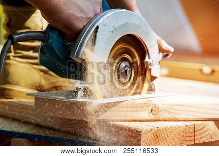 New Home Constructiion Project Building Contractor Worker Using Hand Held Worm Drive Circular Saw To
