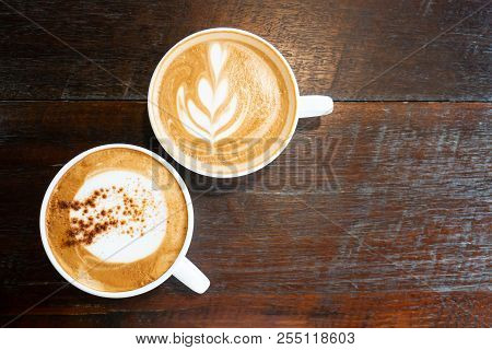 Cup Of Hot Cappuccino And Latte Art Coffee On Wooden Table In The Coffee Shop, Top View