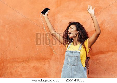 Happy Arab Girl Listening To Music And Dancing With Earphones Outdoors. African Woman In Casual Clot
