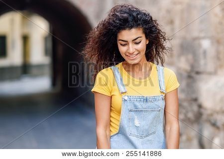 Young Arab Woman With Curly Hairstyle Outdoors. Arab Girl In Casual Clothes In The Street. Happy Fem