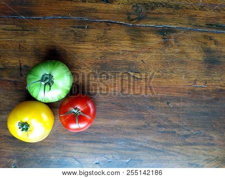 Tasty Heirloon Tomatoes In Yellow, Red And Green On A Wooden Surface