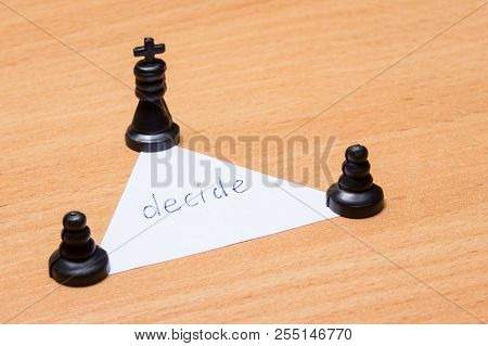 Two Pawns And A Chess King Stand On A Triangle With The Inscription To Decide