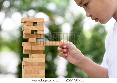 Selective Focus On Kid Hand Play With Wood Block To Build Tower
